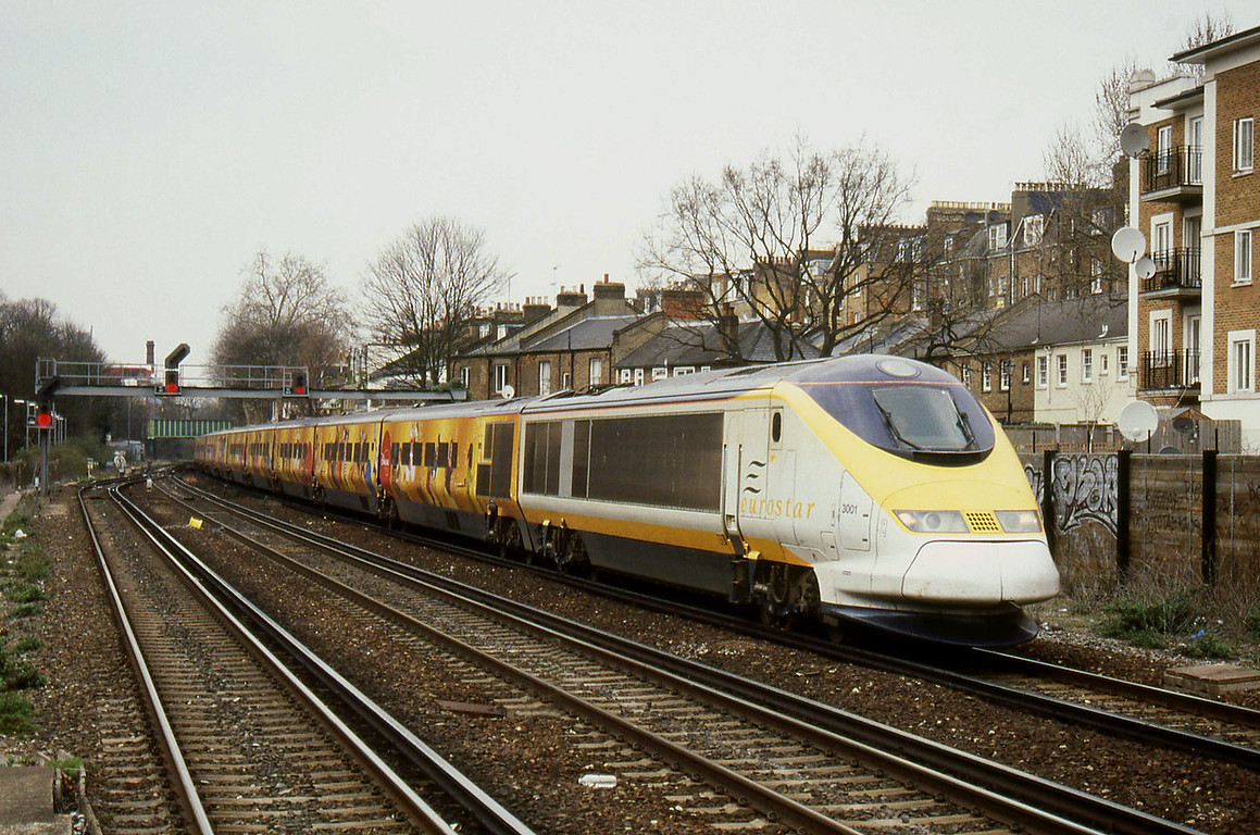 "-- 2004 -- An empty stock working from Eurostar's North Pole Depot in West London to the Eurostar Terminal at London Waterloo heads south through Kensington Olympia led by Class 373 power-car #3001, with the stock in ""Disneyland Resort"" livery."